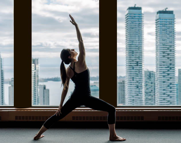 Woman doing yoga, with Toronto skyline in the background