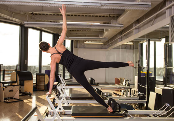 Member of Pilates team on reformer in Pilates Studio