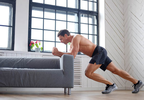 Man doing a leg workout, leaning on his couch