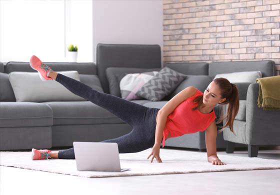 Woman doing a side leg lift in her living room