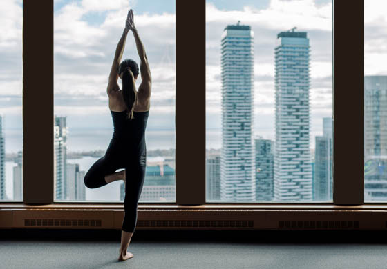 Member in yoga pose in the gym, city skyline in the background