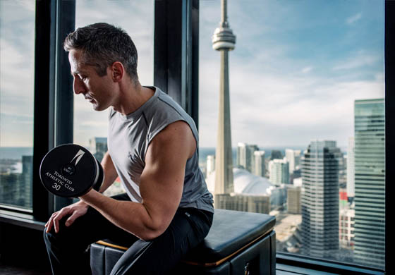 David McCarroll, one of our Personal Trainers, doing bicep curls in the Gym with CN Tower in the background
