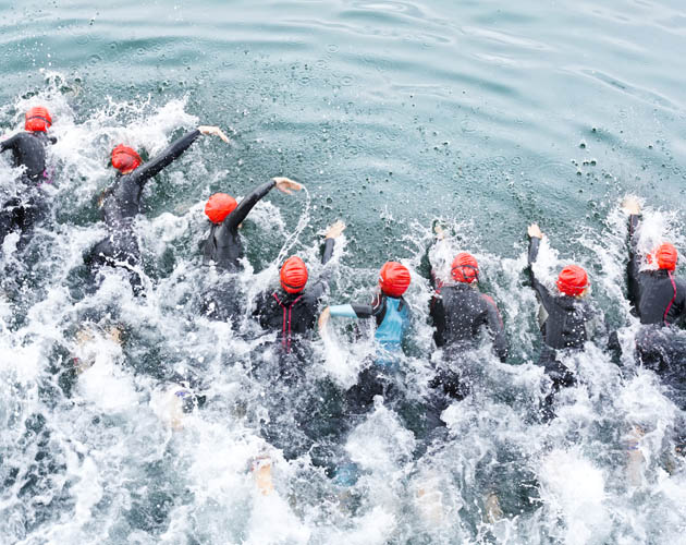 People swimming in a lake, as part of a triathlon