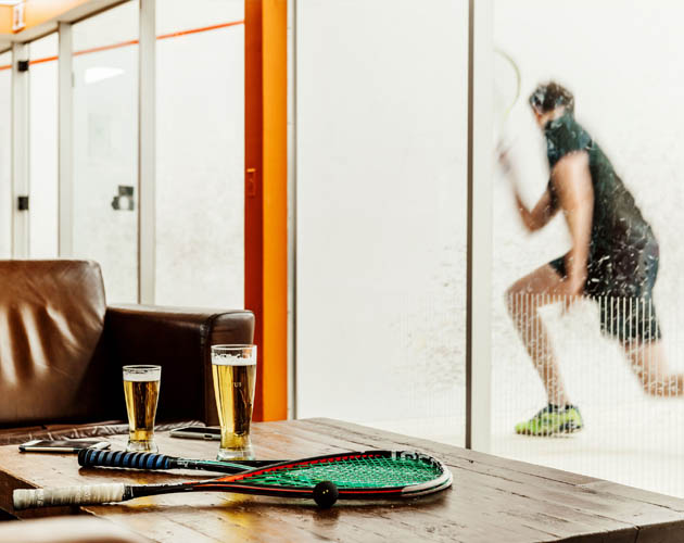 Member playing squash, with beers and squash racquet in the foreground