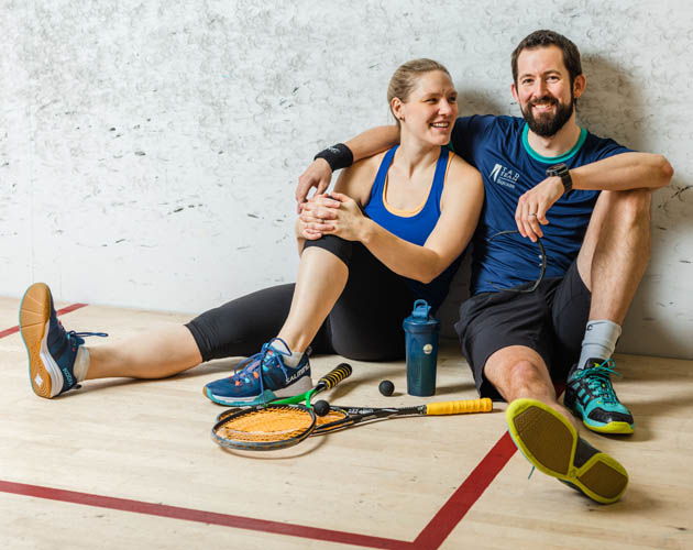 2 of our Members sitting on a squash court at the Toronto Athletic Club